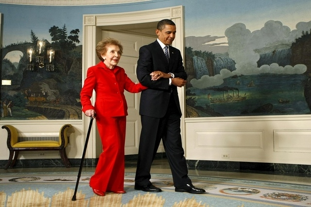 U.S. President Barack Obama escorts former first lady Nancy Reagan to a signing ceremony for the Ronald Reagan Centennial Commission Act in the Diplomatic Reception Room of the White House in Wash ...