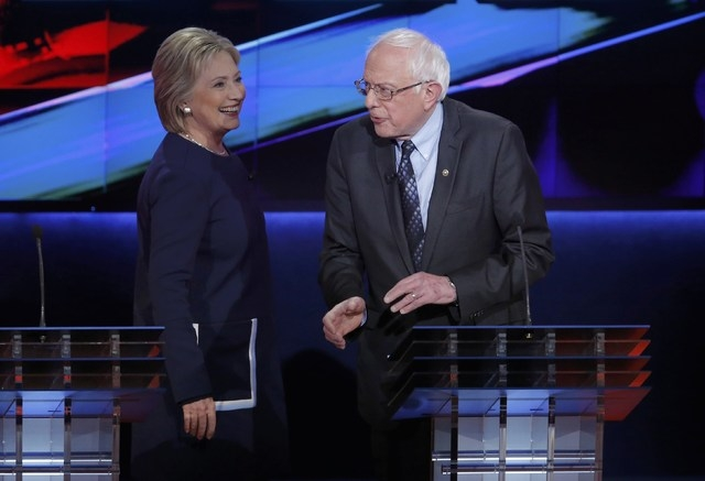 Hillary Clinton and Bernie Sanders talk during a commercial break at the Democratic U.S. presidential candidates' debate in Flint, Mich., on Sunday. (REUTERS/Jim Young)