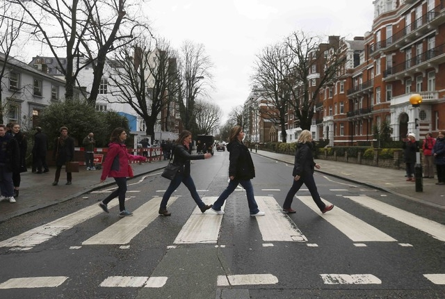 "Tourists walk on a zebra crossing to recreate the ""Abbey Road"" album cover by The Beatles, outside the Abbey Road recording studios in London, March 9, 2016. (Phil Noble/Reuters)"