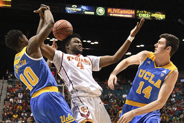 March 9, 2016; Las Vegas, NV, USA; Southern California Trojans forward Chimezie Metu (4) is defended by UCLA Bruins guard Isaac Hamilton (10) and forward Gyorgy Goloman (14) during the second half ...