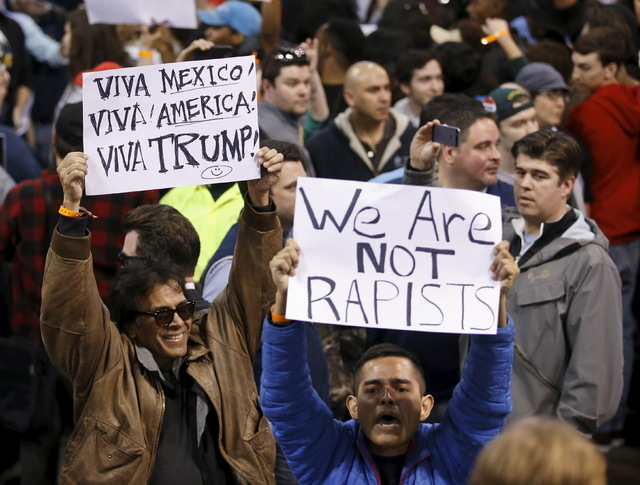 Demonstrators hold signs and cheer after Donald Trump cancelled his rally at the University of Illinois at Chicago on Friday. (Kamil Krzaczynski/Reuters)