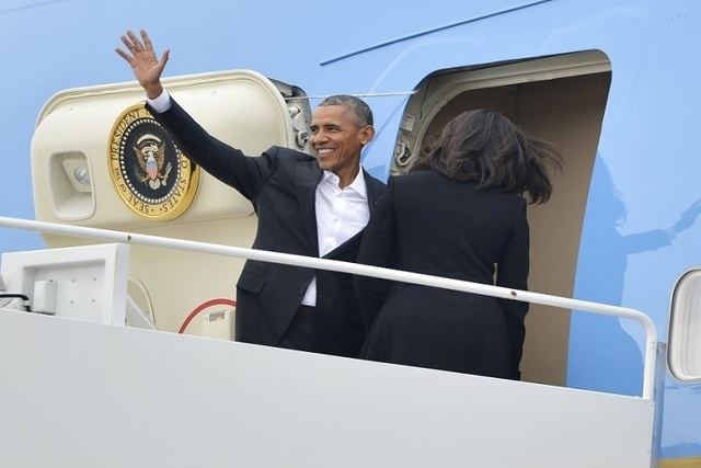 U.S. President Barack Obama waves as first lady Michelle Obama enters the door of Air Force One at Joint Base Andrews, Maryland, for their historic visit to Cuba, March 20, 2016. (REUTERS/Mike The ...