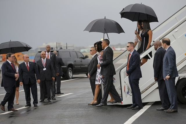 U.S. President Barack Obama and his wife Michelle approach Cuba's foreign minister Bruno Rodriguez (L) as they arrive at Havana's international airport for a three-day trip, in Havana March 20, 20 ...