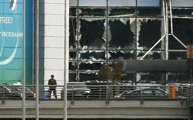 A soldier stands near broken windows after explosions at Zaventem airport near Brussels, Belgium, March 22, 2016. REUTERS/Francois Lenoir