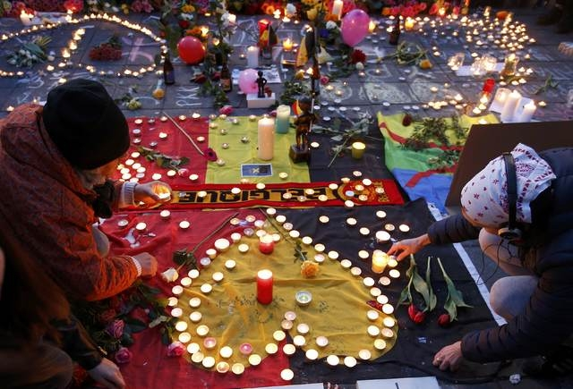 People gather around a memorial in Brussels following bomb attacks in Brussels, Belgium, March 22, 2016.    (Charles Platiau/Reuters)