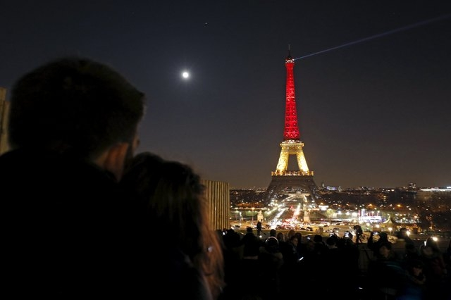 A couple looks at the Eiffel Tower lit up in the colours of the Belgian flag in tribute to the victims of today's bomb attacks in Brussels, in Paris, France, March 22, 2016. (Philippe Wojazer/Reuters)