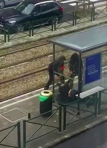 Belgian police drag a suspect along a tramway platform, in this still image taken from amateur video, after the suspect was shot, in the Brussels borough of Schaerbeek, following Tuesday's bombing ...