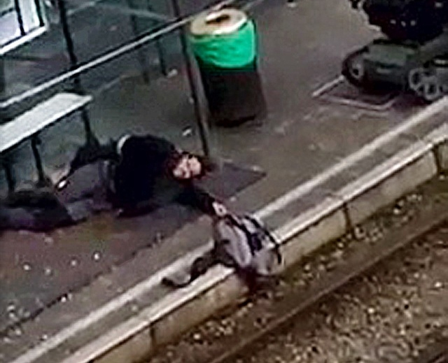 A suspect lies on the platform of a tramway station, in this image taken from amateur video, after he was shot and wounded by police in the Brussels borough of Schaerbeek following Tuesday's bombi ...