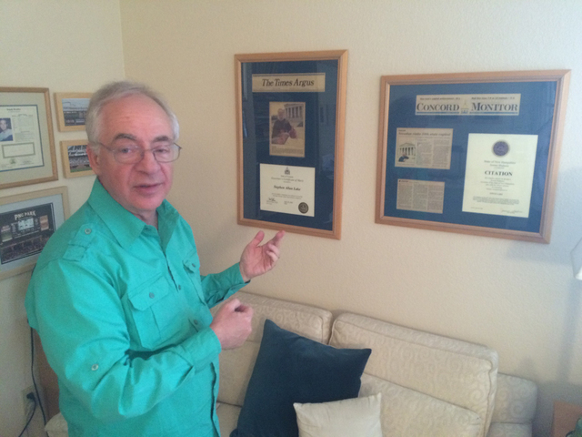 Steve Lake points to some of the framed recognition he's received from some of the the colleges that he and his wife, Caroline, have visited. Jan Hogan/View