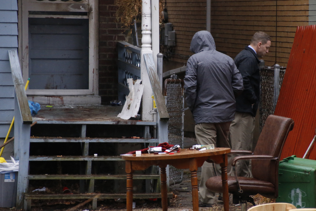 Allegheny County detectives look over the scene of a shooting on Thursday, March 10, 2016, in Wilkinsburg, Pa. Police say five people were killed in the shooting late Wednesday and three were inju ...