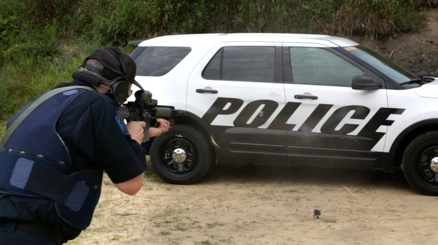 In this July 16, 2015, photo provided by Ford Motor Company, a Michigan State Police officer shoots at the doors of a Ford Police Interceptor Utility vehicle during ballistic testing of doors agai ...