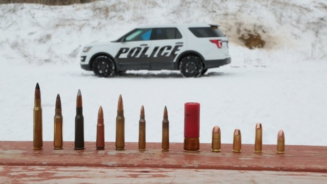 In this March 3, 2016, photo provided by Ford Motor Company, different types of ammunition used in testing are displayed, foreground, as a Ford Police Interceptor Utility vehicle sits parked in th ...