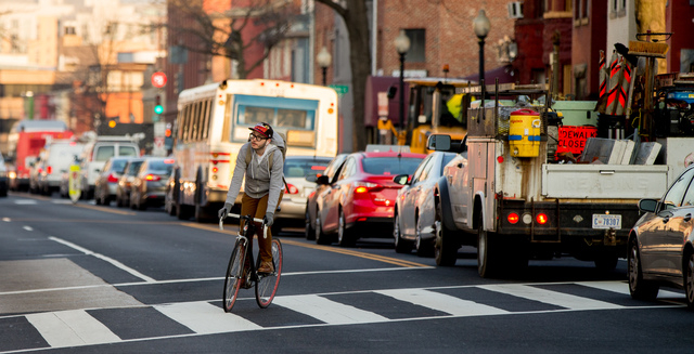 A bicyclist moves past cars stuck in traffic along Florida Avenue in the Shaw neighborhood, in Washington, Wednesday, March 16, 2016. The Metro subway system that serves the nation's capital and i ...