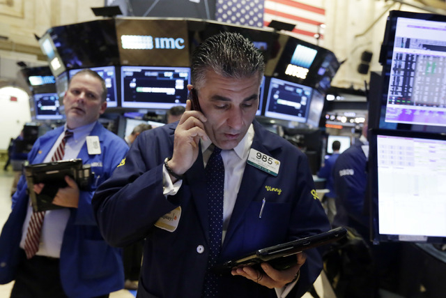 Trader Vincent Quinones, foreground, talks on his phone on the floor of the New York Stock Exchange, Wednesday, March 16, 2016. U.S. stocks are opening slightly lower despite a raft of generally p ...