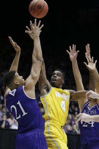 Southern University's Chris Thomas (4) shoots against Holy Cross' Malachi Alexander (21) during the second half of a First Four game of the NCAA college basketball tournament, Wednesday, March 16, ...