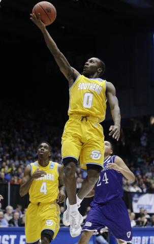 Southern University's Christopher Hyder (0) shoots as Chris Thomas (4) and Holy Cross' Eric Green (24) watches during the second half of a First Four game of the NCAA college basketball tournament ...