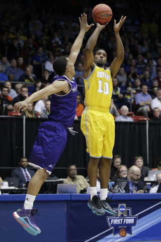 Southern University's Shawn Prudhomme (10) shoots against Holy Cross' Eric Green during the second half of a First Four game of the NCAA college basketball tournament, Wednesday, March 16, 2016, i ...