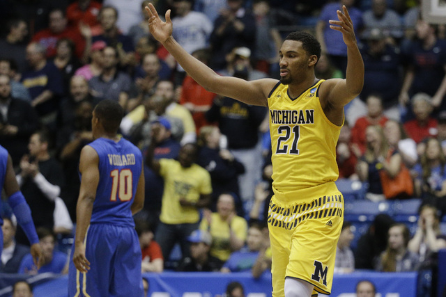 Michigan's Zak Irvin (21) celebrates during the second half of a First Four game of the NCAA college basketball tournament against Tulsa, Wednesday, March 16, 2016, in Dayton, Ohio. Michigan won 6 ...