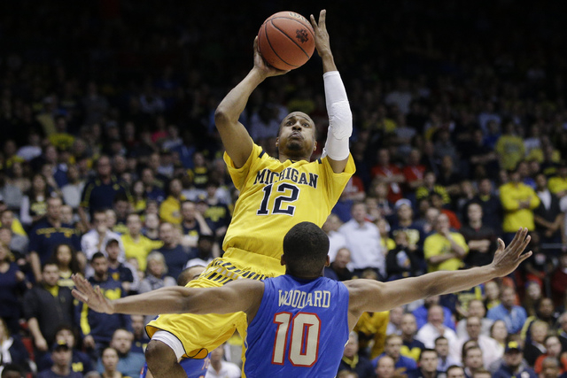 Michigan's Muhammad-Ali Abdur-Rahkman (12) shoots over Tulsa's James Woodard (10) during the second half of a First Four game of the NCAA college basketball tournament, Wednesday, March 16, 2016,  ...