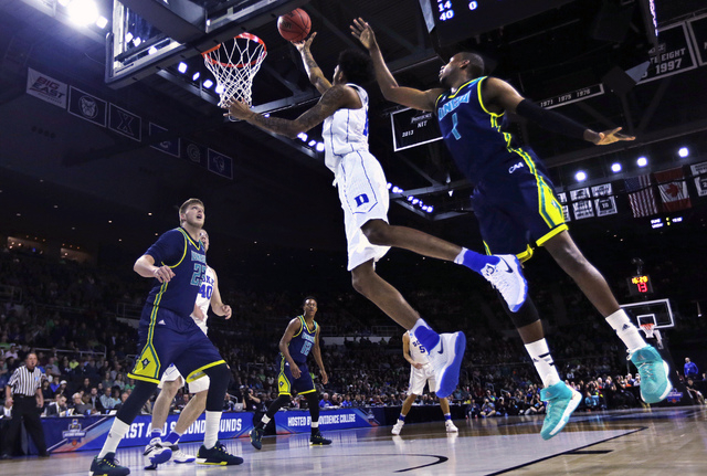 Duke guard Brandon Ingram, center, drives to the basket past North Carolina-Wilmington guard Chris Flemmings (1) during the first half in the first round of the NCAA college men's basketball tourn ...