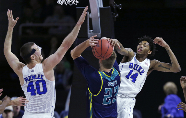 Duke guard Brandon Ingram (14) and center Marshall Plumlee (40) double team North Carolina-Wilmington center C.J. Gettys (23) and block his drive to the basket in the first half during the first r ...