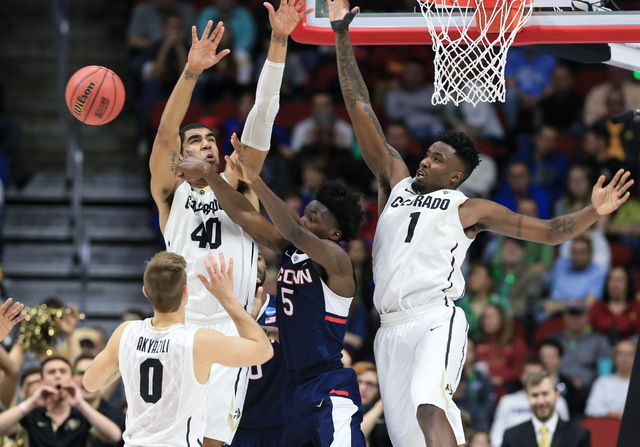 Connecticut's Daniel Hamilton (5) passes the ball while being defended by Colorado's Josh Scott (40), Wesley Gordon (1) and Thomas Akyazili (0), during a first-round men's college basketball game  ...