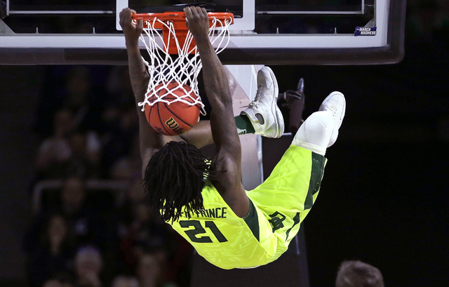 Baylor forward Taurean Prince hangs from on a dunk against Yale during the first half in the first round of the NCAA college men's basketball tournament in Providence, R.I., Thursday, March 17, 20 ...