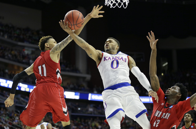 Kansas guard Frank Mason III, center, drives to the basket between Austin Peay defenders Khalil Davis, left, and Kenny Jones, right, during the first half of a first-round men's college basketball ...