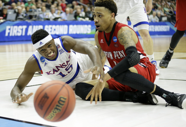 Kansas forward Carlton Bragg Jr., left, fights for the ball with Austin Peay guard Khalil Davis during the first half of a first-round men's college basketball game in the NCAA Tournament, Thursda ...
