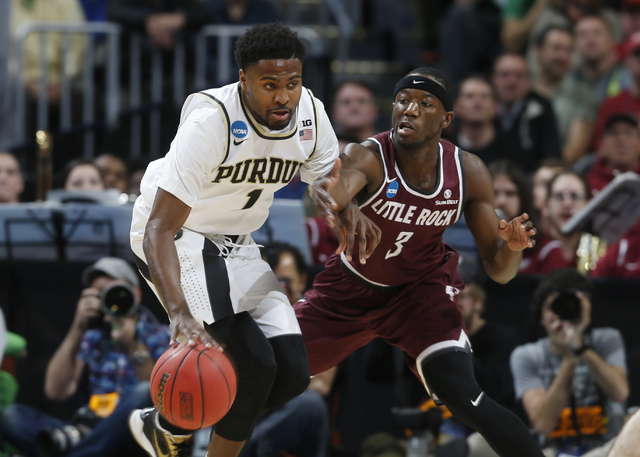 Purdue guard Johnny Hill, left, fights off a potential steal by Arkansas Little Rock guard Josh Hagins in the first half of a first-round men's college basketball game Thursday, March 17, 2016, in ...