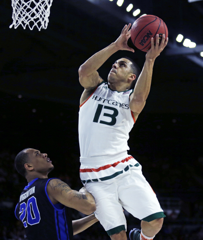 Miami guard Angel Rodriguez (13) drives to the basket against Buffalo guard Rodell Wigginton (20) during the first half of a first-round game in the NCAA college men's basketball tournament in Pro ...