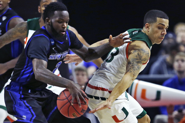 Miami guard Angel Rodriguez, right, tries to steal the ball from Buffalo forward Willie Conner during the first half of a first-round game in the NCAA college men's basketball tournament in Provid ...