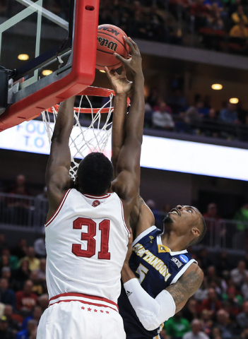 Indiana's Thomas Bryant (31) is fouled by Chattanooga's Justin Tuoyo (5) while attempting a dunk, during a first-round men's college basketball game in the NCAA Tournament in Des Moines, Iowa, Thu ...