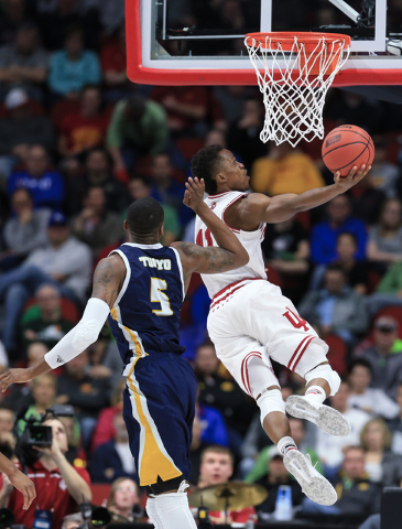 Indiana's Kevin Yogi Ferrell (11) goes to the basket past Chattanooga's Justin Tuoyo (5) during a first-round men's college basketball game in the NCAA Tournament in Des Moines, Iowa, Thursday, Ma ...