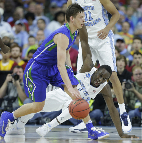Florida Gulf Coast guard Christian Terrell (11) moves the ball by North Carolina forward Theo Pinson (1) during the second half of a first-round men's college basketball game in the NCAA Tournamen ...