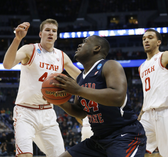 Fresno State center Terrell Carter II, front, goes up for a shot as Utah forwards Jakob Poeltl, back left, and Brekkott Chapman defend in the first half of a first-round men's college basketball g ...