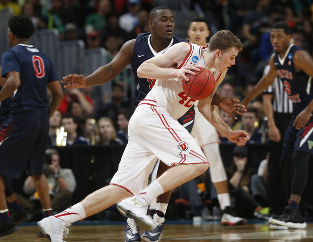 Utah forward Jakob Poeltl, front, drives past Fresno State center Terrell Carter II in the second half of a first-round men's college basketball game Thursday, March 17, 2016, in the NCAA Tourname ...