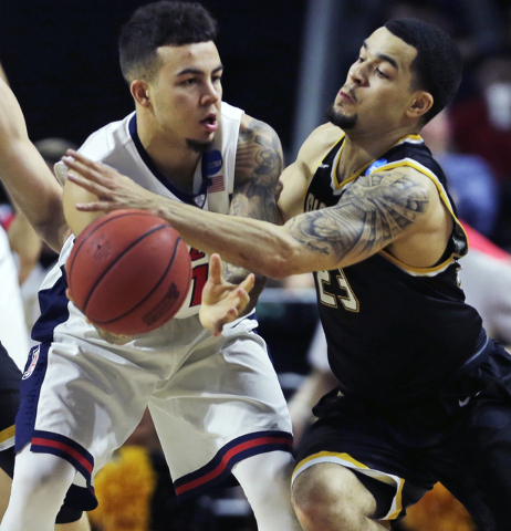 Arizona guard Gabe York, left, is pressured by Wichita State guard Fred VanVleet, right, during the first half of an NCAA college basketball game in the NCAA men's tournament in Providence, R.I.,  ...