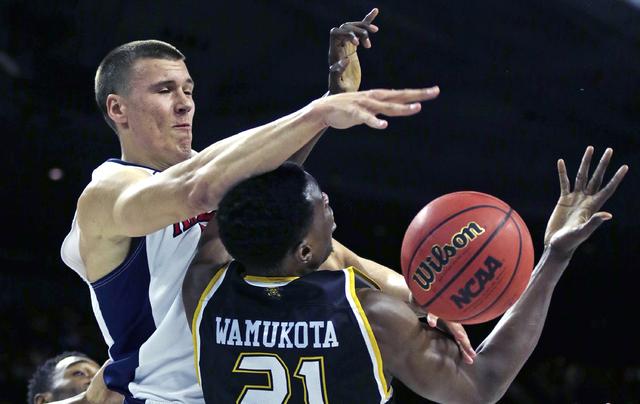 Arizona center Kaleb Tarczewski, left, covers Wichita State center Bush Wamukota (21), who tries to grab a rebound during the first half of a first-round of the NCAA college men's basketball tourn ...