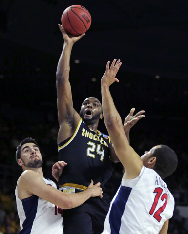 Wichita State forward Shaquille Morris (24) puts up a shot as he is flanked by Arizona forward Ryan Anderson (12) and center Dusan Ristic during the first half of an NCAA college basketball game i ...