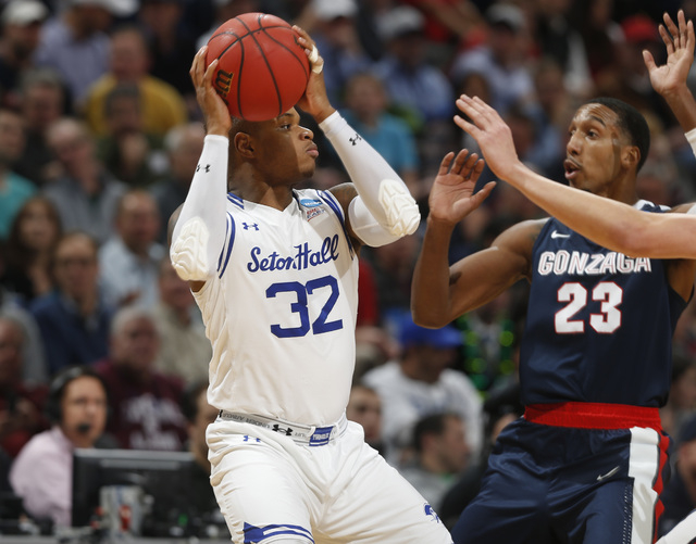 Seton Hall guard Derrick Gordon, left, looks to pass the ball as Gonzaga guard Eric McClellan defends in the first half of a first-round men's college basketball game Thursday, March 17, 2016, in  ...