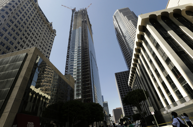 Passerby's look up at the Wilshire Grand Tower on South Figueroa Street where a worker fell to his death on Thursday, March 17, 2016. A fire department spokesperson said the the construction worke ...