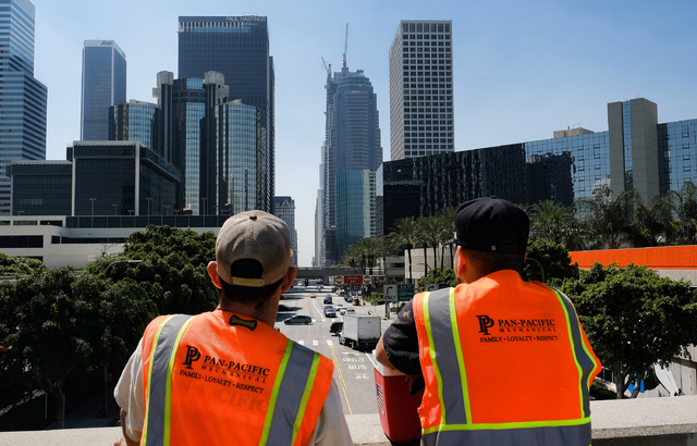 Maintenance workers look down South Figueroa Street toward a skyscraper under construction where a worker fell to his death on Thursday, March 17, 2016. A fire department spokesperson said the the ...