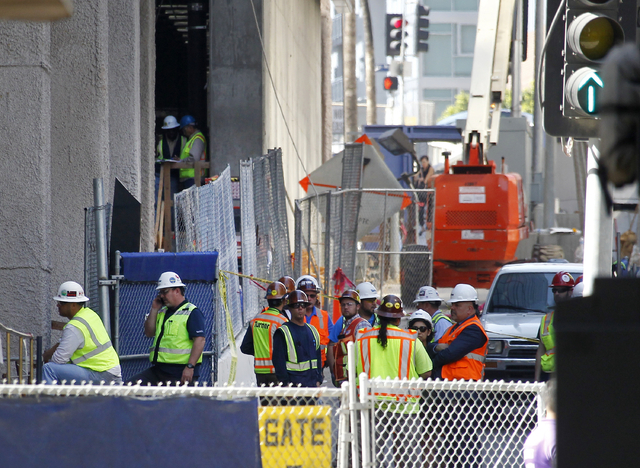 Construction workers gather at the base of the Wilshire Grand Tower on South Figueroa Street where a worker fell to his death on Thursday, March 17, 2016. A fire department spokesperson said the t ...