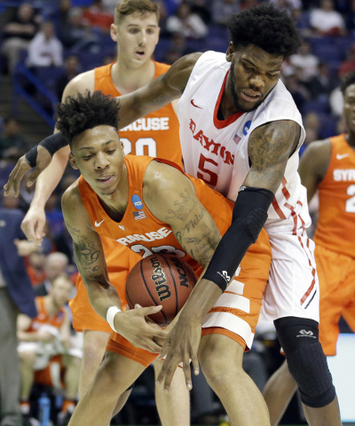 Syracuse's Malachi Richardson, left, tries to control the ball as Dayton's Steve McElvene defends during the first half in a first-round men's college basketball game in the NCAA tournament, Frida ...