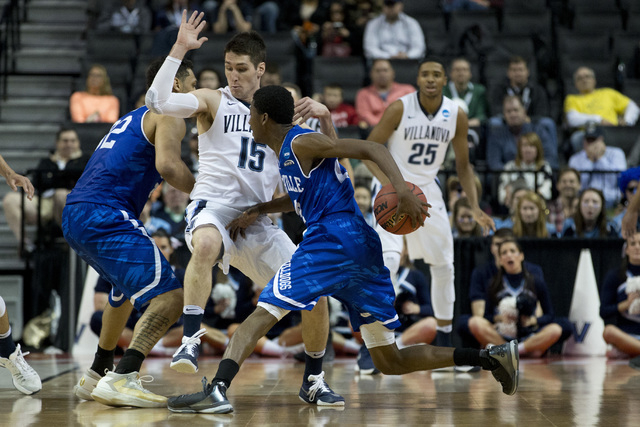 UNC Asheville guard Dylan Smith, center, drives against Villanova guard Ryan Arcidiacono (15) during the first half of a first-round men's college basketball game in the NCAA Tournament, Friday, M ...