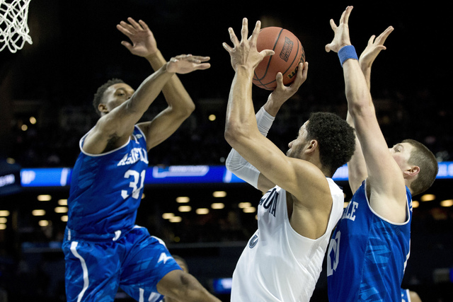 Villanova guard Josh Hart, center, goes to the basket against UNC Asheville forward Sam Hughes (31) and guard Kevin Vannatta (10) during the first half of a first-round men's college basketball ga ...