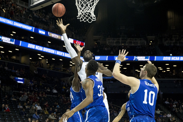 Villanova forward Daniel Ochefu, center, goes to the basket against UNC Asheville forward Sam Hughes (31) and guard Kevin Vannatta (10) during the first half of a first-round men's college basketb ...