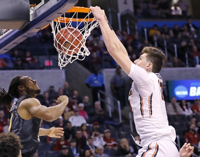 Oregon State forward Drew Eubanks (12) dunks in front of Virginia Commonwealth guard Doug Brooks, left, during the first half of a first-round men's college basketball game in the NCAA Tournament, ...