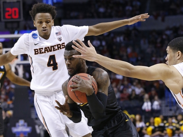 Virginia Commonwealth guard JeQuan Lewis, center, drives to the basket between Oregon State guard Derrick Bruce (4) and guard Malcolm Duvivier, right, in the first half of a first-round men's coll ...